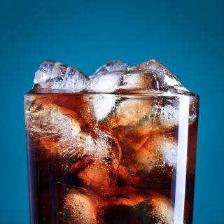 A glass of soda with ice in it.