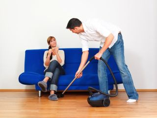 A man vacuums under a couch while a woman sits, filing her nails.