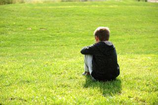 A boy sitting alone on the grass.