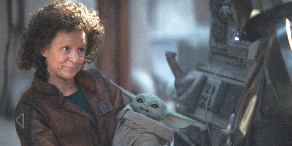 Amy Sedaris as Peli Motto holding Baby Yoda in The Mandalorian
