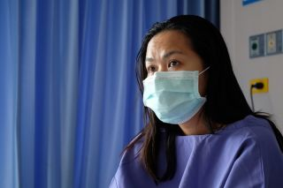A stock photo of a patient in the hospital wearing a face mask.