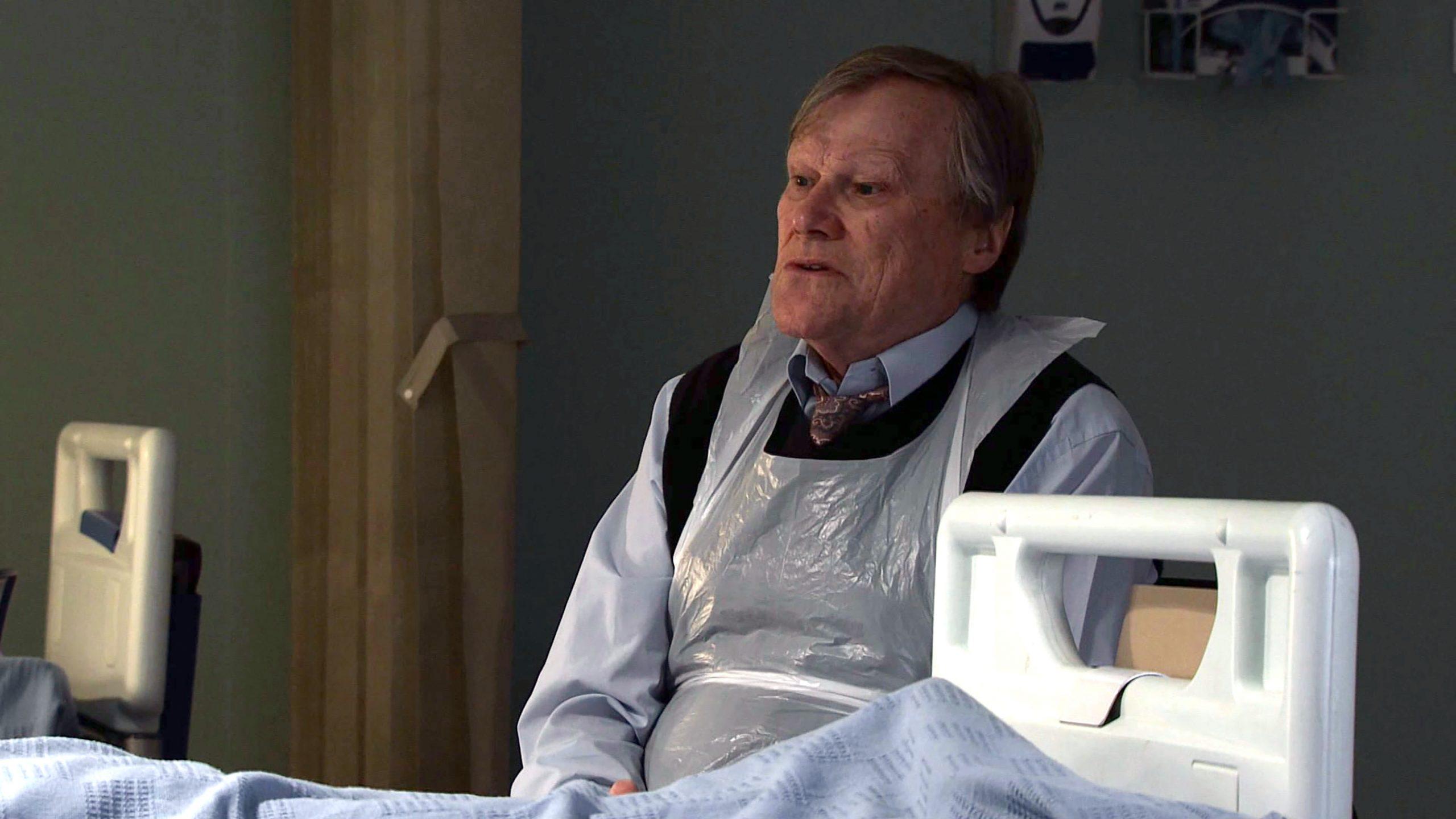 Roy se sienta junto a la cama de hospital de Nina en Coronation Street.