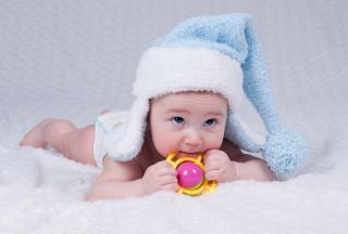a cute newborn baby with a pale-blue winter hat on.