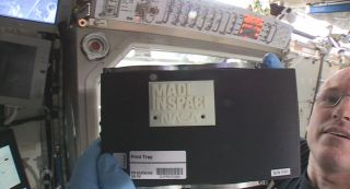 "International Space Station commander Barry ""Butch"" Wilmore holds up the first 3D printed part made in space. The part, an extruder plate (a piece of the printer itself), was made on Nov. 24, 2014."