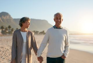 An older couple taking a walk on the beach.