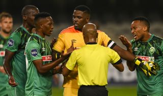 Siyabonga Mbatha tries to keep the players calm during a penalty disagreement