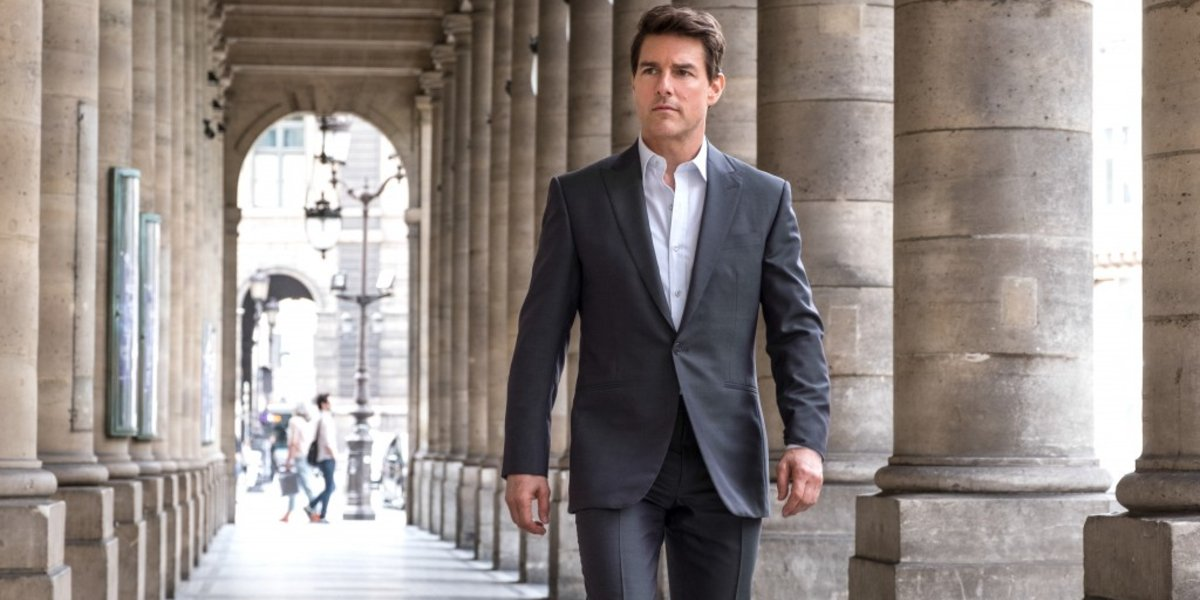 Tom Cruise dressed in a suit, walking during the day in Mission: Impossible - Fallout.