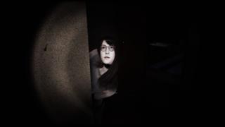 A girl peeks around a corner in a dark room