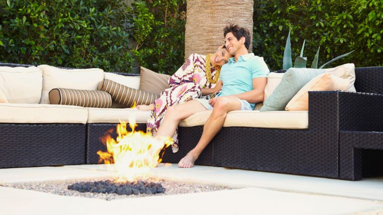B&M fire pits, chimineas, and outdoor heaters, Happy young couple at home, seated by a firepit outdoors