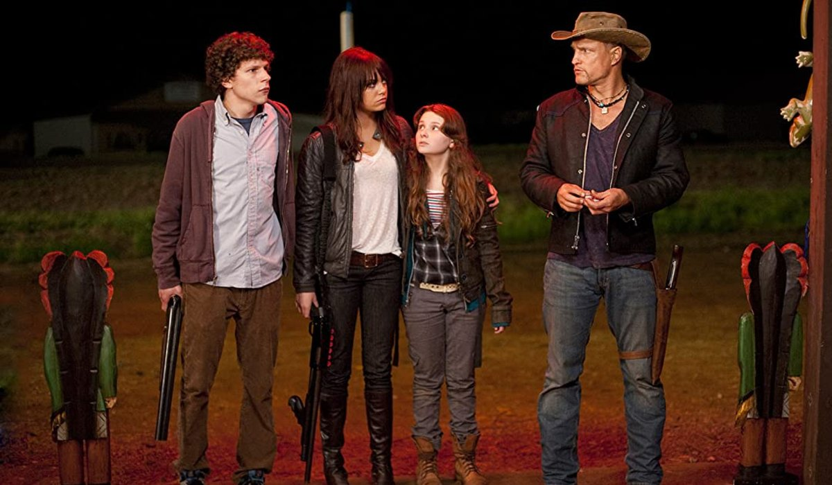 Jesse Eisenberg, Emma Stone, and Abigail Breslin standing outside with Woody Harrelson in Zombieland.