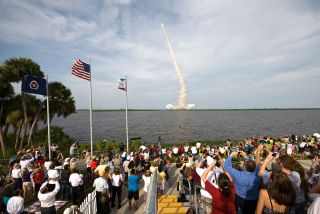 Crowds watch a space shuttle launch
