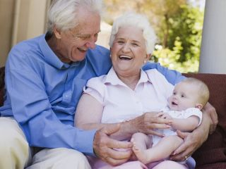 Grandmother and grandfather hold their infant grandchild.
