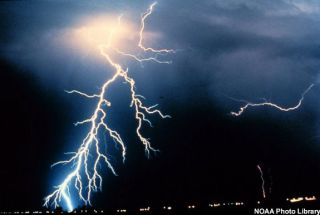 Multiple cloud-to-cloud and cloud-to-ground lightning strokes during a night-time thunderstorm.