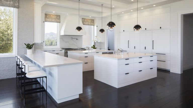 A modern white kitchen with dark floors and black pendant lights