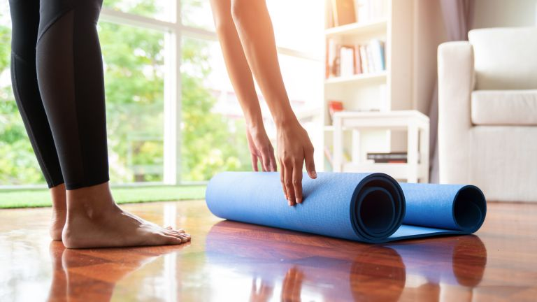 Person rolls up a yoga mat on the floor