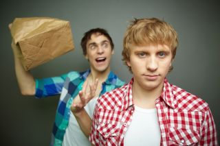 One crazy looking man about to pop a paper bag next to an angry looking man's ear.