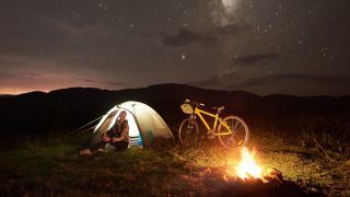 A woman sits by the campfire next to her bike and tent