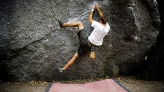 A climber performs a heel hook while bouldering over a red crash pad