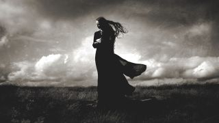 Darkher black and white image on a grassy hill