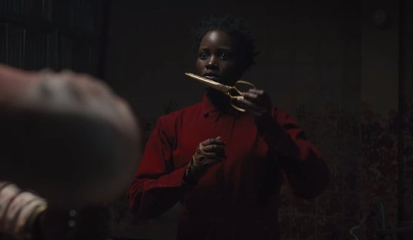 Us Lupita N'yongo holding the scissors in her red jumpsuit, in a darkened room
