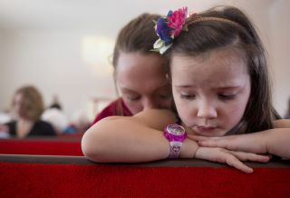 The prescription drug Narcan saved Shannon Long from an opioid overdose. Here, she kneels with her daughter Hope at Woodstock Seventh Day Adventist church on Feb. 4, 2017.