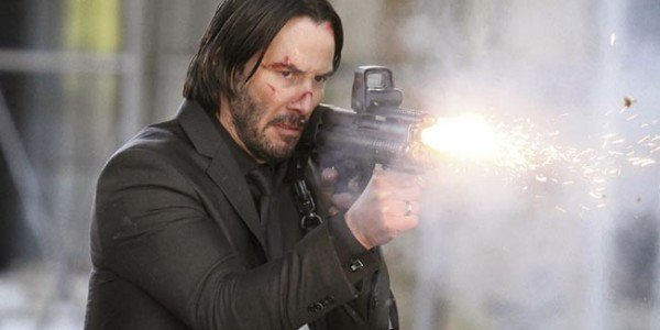 Keanu Reeves as John Wick firing a gun