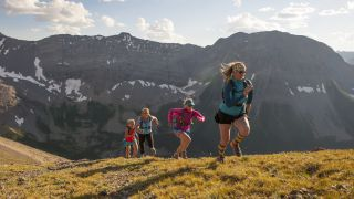 A group of women trail running up a steep mountain