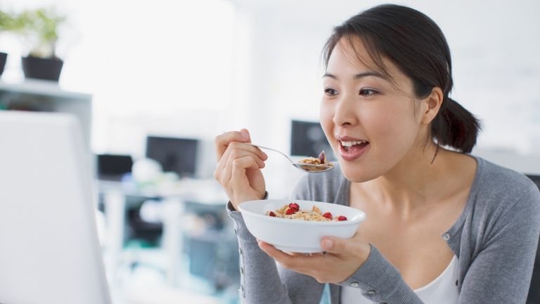 Women eats breakfast out of a cereal bowl and looks happy