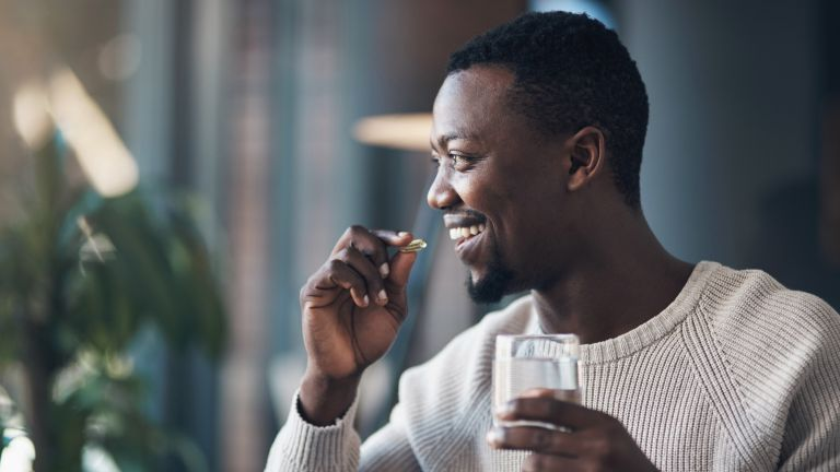 Man is about to put a vitamin pill in his mouth as he holds a glass of water in his other hand
