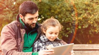 A father reads from a tablet computer with his daughter outdoors