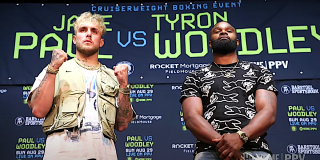 Jake Paul and Tyron Woodley stand for photos at the press conference for upcoming boxing match.