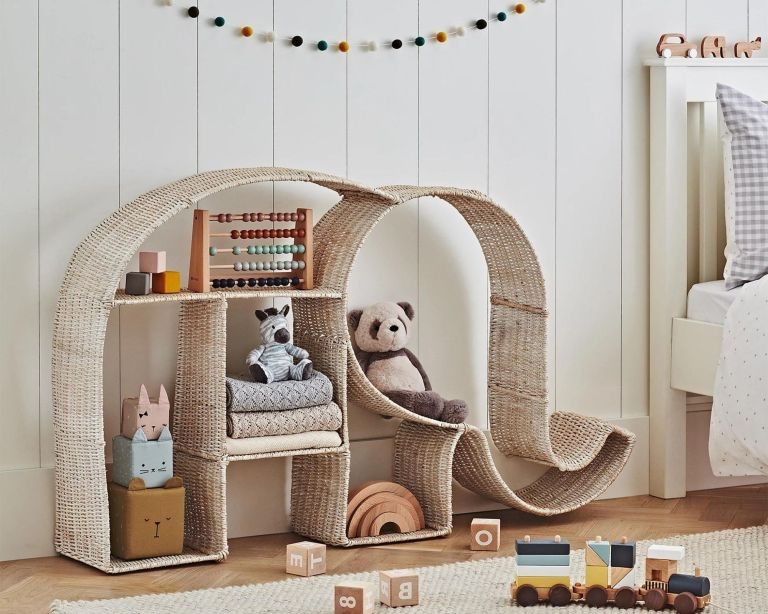 Rattan bookshelf shaped like elephant pushed up against wall in nursery filled with kids toys including an abacus and panda soft toy