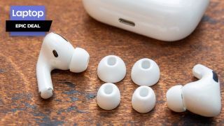 AirPods Pro with silicone ear tips on wooden desk