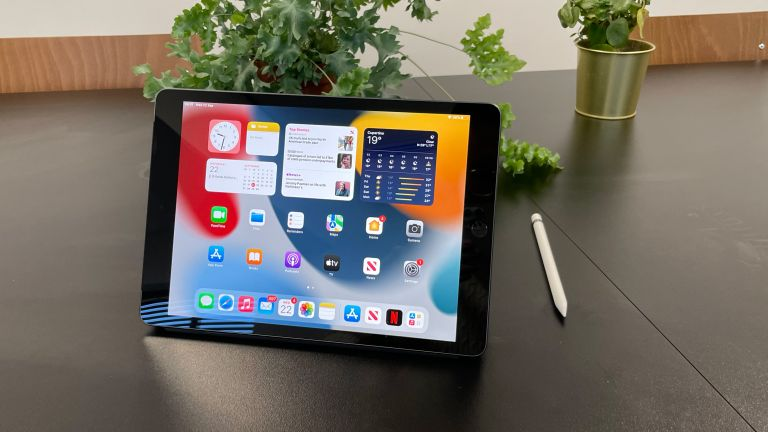 Apple iPad 10.2-inch (9th Gen) review, showing the tablet on a table, in landscape mode, with the Apple Pencil next to it