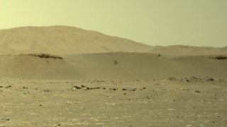 NASA's Mars helicopter Ingenuity takes its third flight on the Red Planet in this zoomed-in view of a photo from the Perseverance rover taken on April 25, 2021.