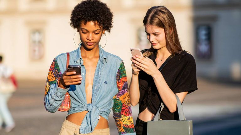 Two young woman are looking at their phone wearing fashionable outfits, this was pictures during fashion month in Italy