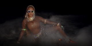 Beyonce sits on the ground while wearing a glittery bodysuit and sequined sunglasses in a scene from 'Black Is King'