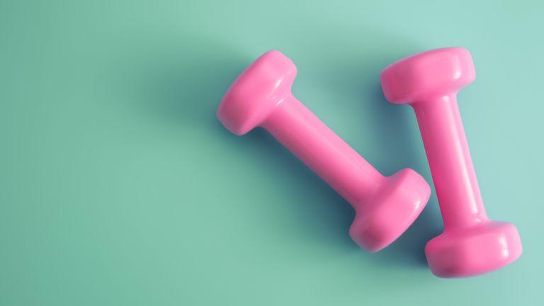 pink dumbbells on green background for strength training for women