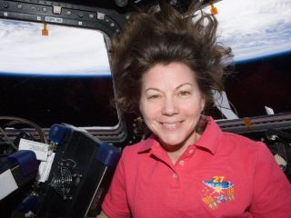 NASA astronaut Cady Coleman, Expedition 27 flight engineer, is pictured in the Cupola of the International Space Station. Earth's horizon and the blackness of space are visible through the windows.