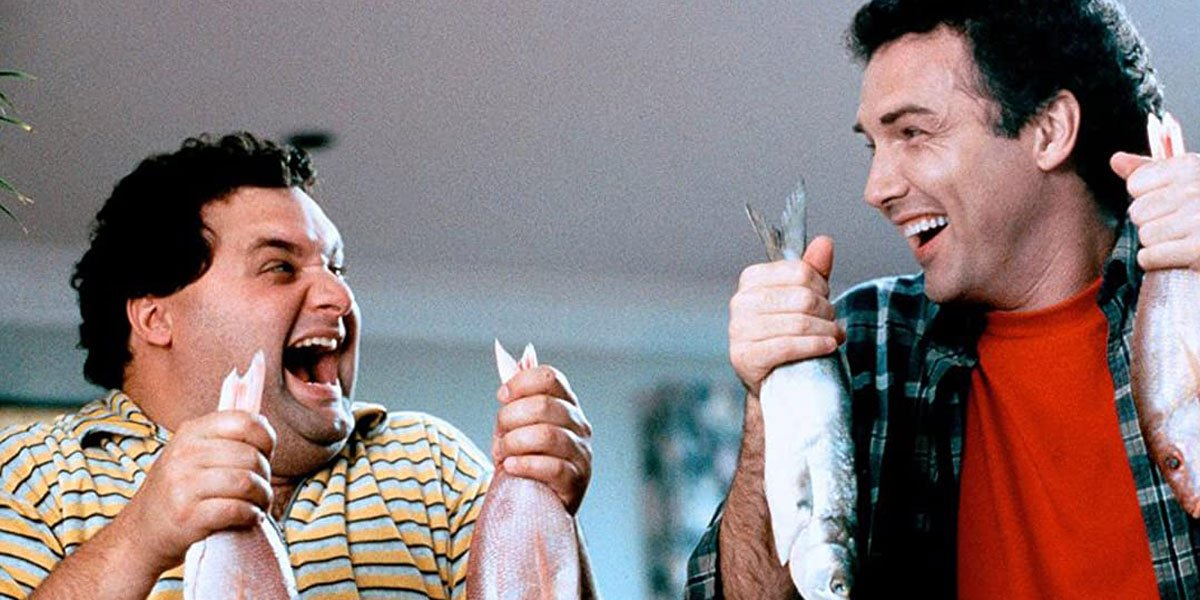 Norm and Artie laughing while holding fish in Dirty Work.