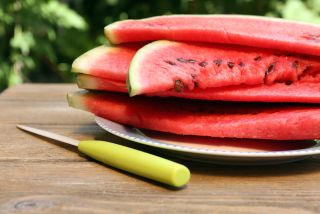 A pile of cut watermelon sits on a picnic table.