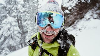 A skier wearing goggles is smiling and snow covered on a powder day