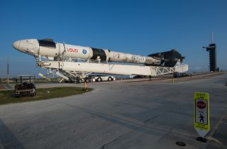 Rolling down the road is a SpaceX Falcon 9 rocket with the company's Crew Dragon spacecraft attached in preparation for the launch of the Crew-2 mission. Crew-2 is expected to launch from NASA's Kennedy Space Center in Florida from Pad 39A on Thursday April 22.