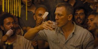 Daniel Craig as James Bond playing a drinking game in Skyfall
