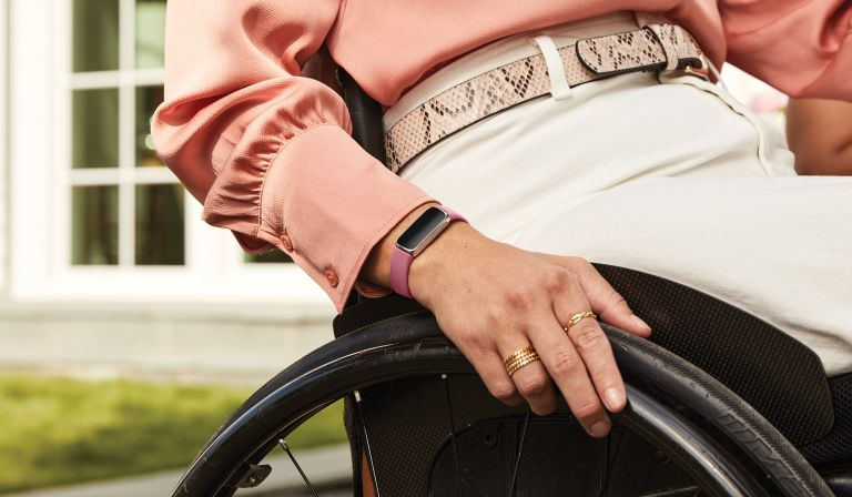 Woman in a wheelchair wearing a Fitbit Luxe