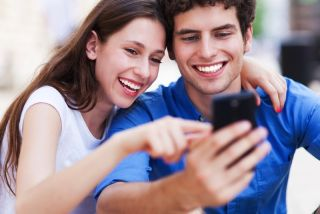 A young couple takes a picture of themselves using a smartphone.