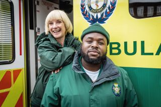 Bloods: Wendy (Jane Horrocks) and Maleek (Samson Kayo) in uniform outside an ambulance. Wendy is leaning on Maleek's shoulder.
