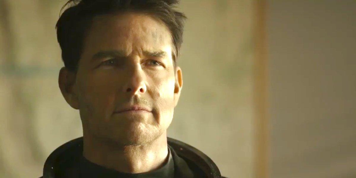 Tom Cruise standing in a briefing room, wearing his flight suit in Top Gun Maverick.