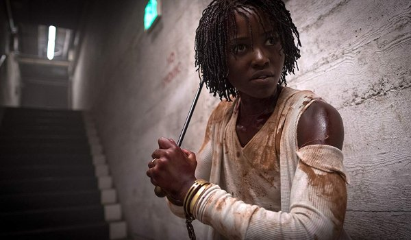 Us Lupita N'yongo holding a weapon as she makes her way underground
