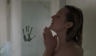 The Invisible Man puts his hand on the shower door, as Elizabeth Moss isn't looking